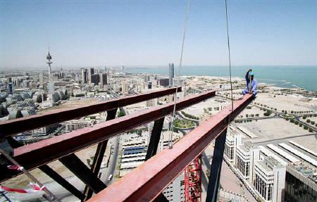 A construction worker sits on a steel beam atop a new 30-floor high-rise building in Kuwait city on July 6, 2004. Gulf Arab countries must end their sponsorship system for migrant workers that leaves labourers beholden to employers and exposed to potential abuse, the U.N. High Commissioner for Human Rights said. REUTERS/Stephanie McGehee/Files