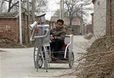 <p>Farmer Wu Yulu, 48, operates his walking robot near his home in a village at the outskirts of Beijing April 14, 2010. REUTERS/Petar Kujundzic</p>