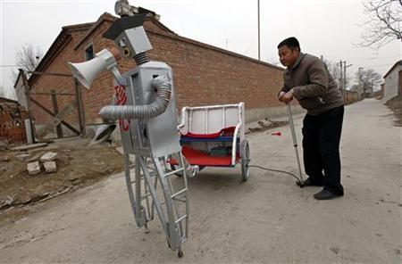 Farmer Wu Yulu, 48, pumps air to a wheel of a cart pulled by his walking robot near his home in a village at the outskirts of Beijing April 14, 2010. REUTERS/Petar Kujundzic
