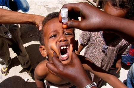 A health worker drops anti-polio vaccine into the mouth of a Somali child in the capital Mogadishu September 10, 2006. REUTERS/Shabelle Media