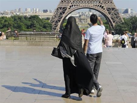 A woman wearing a niqab walks at Trocadero square near the Eiffel Tower in Paris June 24, 2009. France is moving towards a ban on wearing face-covering Islamic veils in public, with the government set to examine a draft bill next month amid heated debate over women's rights and religious freedom. REUTERS/Gonzalo Fuentes/Files
