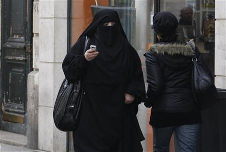 A woman wears a burqa as she walks on a street in Saint-Denis, near Paris, April 2, 2010. REUTERS/Regis Duvignau