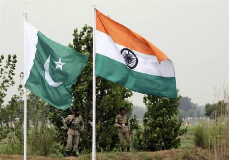 Pakistani rangers stand near the Indian (R) and Pakistani national flags near Pakistan border in Chamliyal, 45 km (28 miles) west of Jammu, June 26, 2008. Leaders of India and Pakistan are likely to meet in Bhutan's capital next week as their nuclear-armed rivalry overshadows a summit of South Asian nations. REUTERS/Amit Gupta/Files