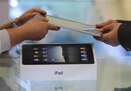A customer (R) buys an iPad at an electronic products store in Hefei, Anhui province April 22, 2010. The iPad sells for about 5900 yuan (US$864). REUTERS/Stringer