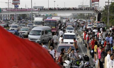 Anti-government 'red-shirt' protesters block a main road leading into Bangkok about 30km (18 miles) north of the city April 25, 2010. REUTERS/Sukree Sukplang