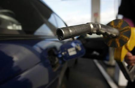 A motorist prepares to put fuel into her car at a petrol station in Melbourne July 3, 2008. REUTERS/Mick Tsikas/Files