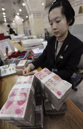 An employee counts Chinese yuan banknotes at a branch of Bank of China in Hefei, Anhui province March 5, 2010. REUTERS/Stringer