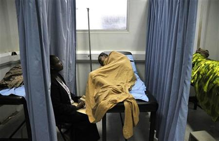 An attendant cares for a patient infected with HIV/AIDS in a ward in Uganda's Infectious Disease Institute in the capital Kampala June 5, 2008. REUTERS/James Akena