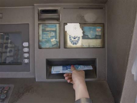 A woman draws money from an ATM machine in Tehran May 4, 2008. REUTERS/Morteza Nikoubazl/Files