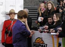 <p>Fans ask for an autograph from singer Justin Bieber on the red carpet of the Juno Awards outside the Mile One stadium in St. John's, Newfoundland April 18, 2010. REUTERS/Greg Locke</p>