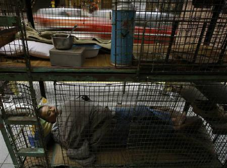 A former cage home resident sleeps in a caged-bed displayed on a street at Hong Kong's financial Central district as a gesture to bring public awareness to the poor in the territory April 29, 2009. REUTERS/Bobby Yip