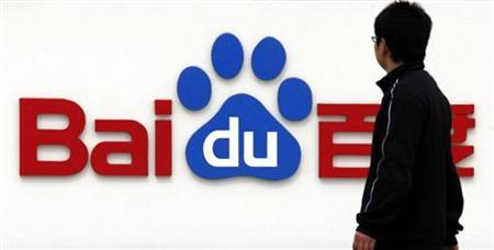 A pedestrian looks at the company logo of Baidu as he walks past their headquarters in Beijing March 24, 2010. REUTERS/David Gray