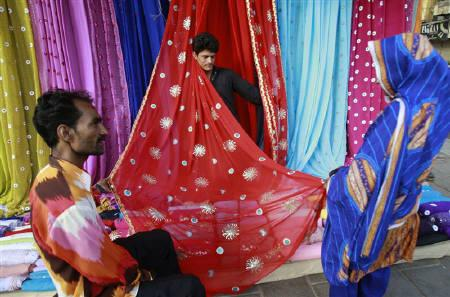 Men display fabric to a woman on the streets of Karachi June 21, 2009.   REUTERS/Athar Hussain/Files