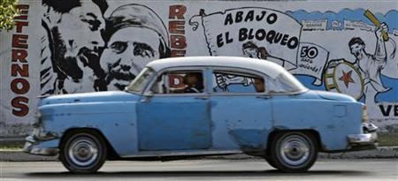 A motorist drives past a mural depicting former Cuban leader Fidel Castro and late revolution leader Ernesto Che Guevara (L) on a wall in Havana April 22, 2010. The mural reads, ''Eternal rebels'' (L) and ''Down with the blockade'', referring to U.S. trade embargo, which has been in place against the communist-ruled island since 1962. REUTERS/Desmond Boylan