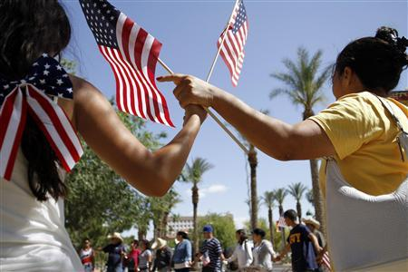 People hold hands and pray as they protest against Senate Bill 1070 outside the Arizona State Capitol in Phoenix, Arizona April 29, 2010. REUTERS/Joshua Lott