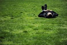 <p>A man takes a break on a sunny day on the grass of LaFayette Park near the White House in Washington, April 22, 2010. REUTERS/Jonathan Ernst</p>