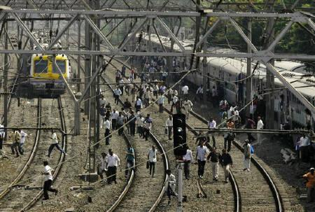 Commuters cross railway tracks in Mumbai May 4, 2010. A strike by motormen of Mumbai's famed suburban trains, which threw city travel out of gear, was called off on Tuesday evening, following an assurance their demands would be looked into, officials said. REUTERS/Arko Datta
