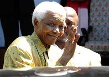 <p>Ex-presidente da África do Sul Nelson Mandela acena depois de deixar reunião com ex-presos políticos em Robben Island, Cidade do Cabo. A taça da Copa do Mundo foi entregue a Nelson Mandela nesta quinta-feira, quando começou o último trecho da viagem ao redor do mundo do troféu, 35 dias antes da abertura do Mundial. 12/02/2010. REUTERS/Elmond Jiyane/Divulgação</p>