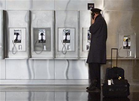 A pilot talks on the phone at Reagan National Airport near Washington February 17, 2003. REUTERS/Brendan McDermid