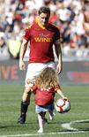 <p>Il capitano della AS Roma Francesco Totti oggi all'Olimpico alla fine della partita col Cagliari, mentre gioca con la figlia. REUTERS/Alessandro Bianchi</p>