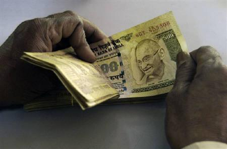 A bank employee counts currency notes at a cash counter inside a bank in Agartala February 26, 2010. REUTERS/Jayanta Dey/Files