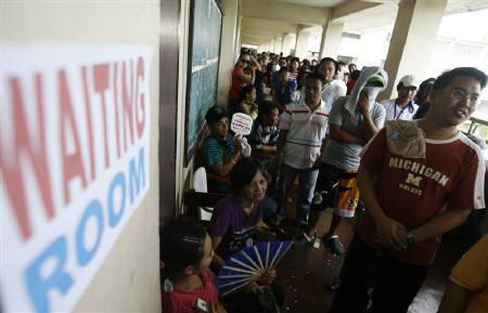 Voters wait in line during election day at a polling precinct in Manila May 10, 2010. The Philippines' elections agency will release partial and unofficial tallies of votes for president and other national and local positions at 9 p.m. on Monday, the head of the poll body said. REUTERS/Cheryl Ravelo