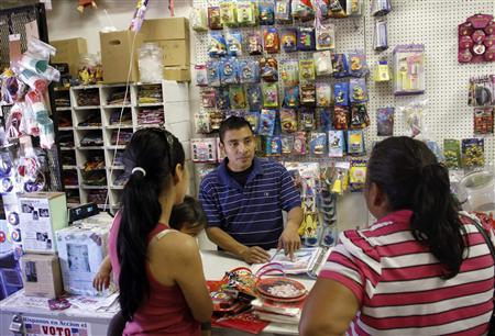 Oswaldo Alvarado helps customers at Importaciones Valentinas grocery and pinata store in Phoenix, May 11, 2010. REUTERS/Joshua Lott