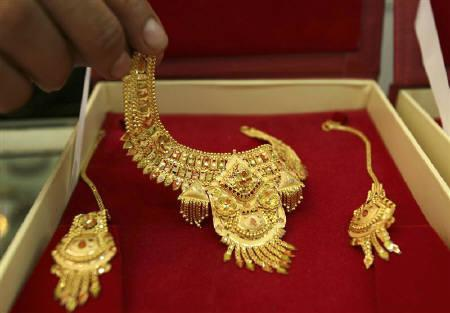 A shopkeeper displays gold jewellery for the camera at a jewellery shop in Jammu in this July 2009 file photo. REUTERS/Mukesh Gupta/Files