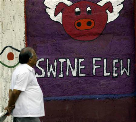 A man walks past a graffiti about H1N1 influenza on a street side wall in Mumbai September 9, 2009. Cadila Healthcare Ltd said on Wednesday it has received approval from the Drug Controller General of India to market the H1N1 vaccine in the country.  REUTERS/Arko Datta/Files