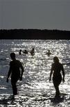 <p>Туристы гуляют по пляжу в турецком городе Кусадаси 17 июля 2005 года. Россия и Турция готовят отмену визового режима для туристов в разгар курортного сезона после того, как вступит в действие соглашение о взаимной выдаче подлежащих депортации мигрантов, сообщили на совместной пресс-конференции в среду лидеры двух государств. REUTERS/Umit Bektas</p>