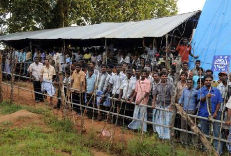Displaced Tamil civilians watch, as Sri Lankan President Mahinda Rajapaksa (not seen) arrives at the Manik Farm refugee camp, on the outskirts of the northern Sri Lankan town of Vavuniya, December 9, 2009. REUTERS/Lakruwan Wanniarachchi/Pool