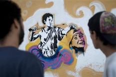 "<p>Street artists who are members of the ""Communicational Liberation Army"", view their completed work in Caracas May 5, 2010. REUTERS/Carlos Garcia Rawlins</p>"