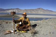<p>A Tibetan pilgrim spins his praying wheel as he stops to pray on the road from Shigatse to Tsedang Tibet Autonomous Region November 26, 2009. REUTERS/Nir Elias</p>