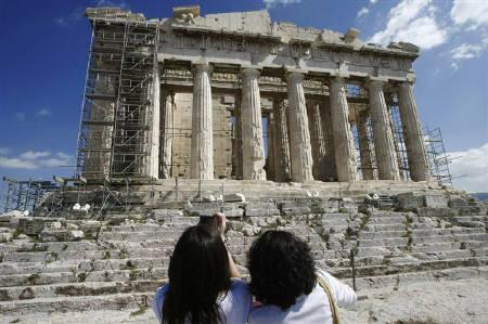 Tourists take photos in front of the Parthenon temple at the Acropolis in Athens, March 18, 2010. REUTERS/John Kolesidis/Files