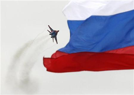 A MiG-29 fighter jet performs a manoeuvre as the Russian national flag flies in the foreground, during the MAKS-2009 international air show in Zhukovsky, outside Moscow, August 22, 2009. REUTERS/Sergei Karpukhin