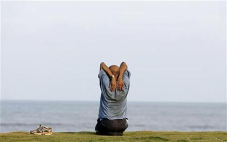 A man practices yoga by the seaside during early morning in Mumbai May 6, 2007. REUTERS/Punit Paranjpe