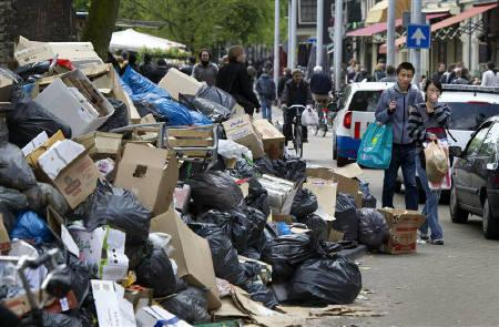 Two tourists look at a pile of rubbish at the Nieuwmarkt in Amsterdam May 14, 2010. Trash collectors in the major cities in the Netherlands have been strike since Queen's Day, April 30, as they demanded higher wages.  REUTERS/Olaf Kraak