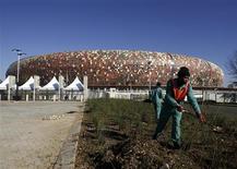 <p>Funcionários de manutenção em frente ao estádio Soccer City em Johanesburgo. Foram anos de dúvidas, inquietações e críticas, mas agora a África do Sul parece prestes a realizar uma Copa do Mundo capaz de impressionar os mais pessimistas. 18/05/2010 REUTERS/Siphiwe Sibeko</p>