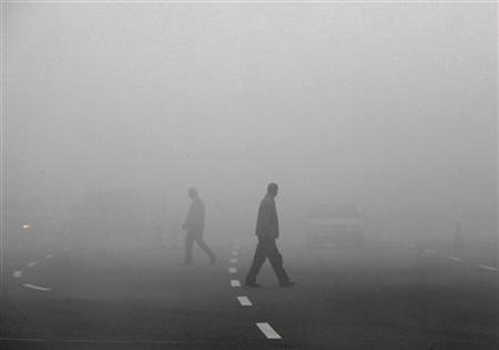 Men cross a road through thick fog in a file photo. REUTERS/David Gray