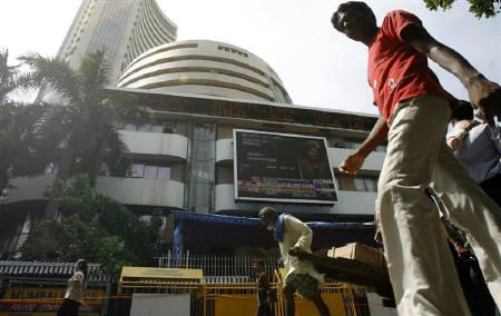 People walk past the Bombay Stock Exchange (BSE) building displaying India's benchmark share index on its facade, September 30, 2009. REUTERS/Punit Paranjpe/Files