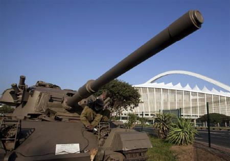 A worker restores a vintage tank opposite Moses Mabhida Stadium in Durban May 21, 2010. The World Cup could be vulnerable to a terrorist attack, despite repeated South African assurances that the tournament is safe and the discovery of what looks like a half-baked plot hatched in Iraq. REUTERS/Rogan Ward