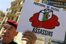 """<p>Manifestante mostra cartaz em protesto contra o filme """"Hors La Loi"""" (""""Fora da Lei""""), do diretor Rachid Bouchareb, que concorre no 63o Festival de Cinema de Cannes, 21 de maio de 2010. O cartaz mostra uma figura com a bandeira da Argélia, com a palavra """"Assassinos"""". Um filme sobre a luta sangrenta pela independência da Argélia estreou na sexta-feira em Cannes em meio a segurança policial intensa, enquanto manifestantes do lado de fora protestavam, dizendo que o filme macula a memória do Exército francês. REUTERS/Eric Gaillard</p>"""