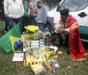 <p>Apresentação de um ritual realizado para desejar sorte à selação brasileira em Curitiba. Uma fumaça verde cobriu a multidão de torcedores que se aglomerou na entrada do centro de treinamento utilizado pela seleção brasileira, enquanto um pai-de-santo vestido a caráter e fumando charuto fazia um trabalho que garantiu que levará o Brasil ao hexa. 21/05/2010 REUTERS/Paulo Whitaker</p>