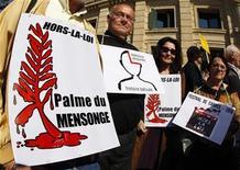 """<p>Manifestantes sostienen carteles en protesta de la película """"Hors La Loi"""" (Fuera de la Ley) en el Festival de Cine de Cannes. Mayo 21 2010. Una película sobre la sangrienta lucha por la independencia de Argelia se presentó el viernes en medio de una reforzada seguridad policial en Cannes, mientras manifestantes en el exterior protestaban porque manchaba la memoria del Ejército francés. REUTERS/Eric Gaillard</p>"""