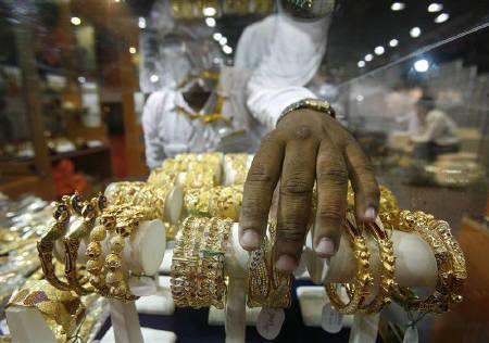 A salesman arranges gold bangles in a stall at a jewellery exhibition in Kolkata in this May 10, 2010 file photo. REUTERS/Parth Sanyal/Files