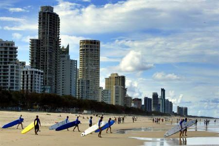 Longboard surfers walk into the water at the popular tourist of Main Beach at Surfer's Paradise, in this October 17, 2003 file photo. REUTERS/David Gray/Files