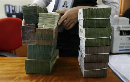 An employee stacks bundles of Vietnamese dong banknotes at a bank in Hanoi April 21, 2010.  REUTERS/Nguyen Huy Kham