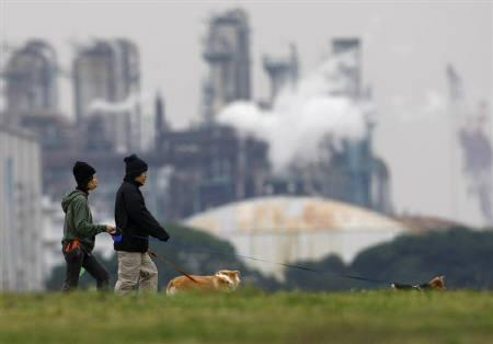 People walk with their dogs near factory emissions at Keihin industrial zone in Kawasaki, south of Tokyo November 12, 2008. Japan may withdraw support for the Kyoto Protocol post-2012, demanding major emitters the United States, China and India sign up to a unified plan to cut greenhouse gases. REUTERS/Toru Hanai/Files