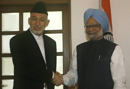 Prime Minister Manmohan Singh (R) shakes hands with Afghanistan's President Hamid Karzai  in New Delhi April 26, 2010. The Obama administration is grappling with how to balance India's role in Afghanistan as arch-rival Pakistan also jostles for influence there. REUTERS/B Mathur/Files