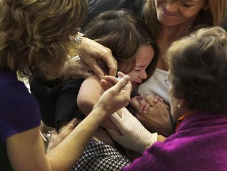 A girl reacts while getting her H1N1 influenza vaccination in Vancouver, British Columbia October 26, 2009. REUTERS/Andy Clark